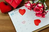 Table top view aerial image of decoration valentine's day background concept.Flat lay arrangement of calendar page of february month with essential items love heart with rose flower on wooden.