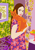 Young woman holding a cat in bright decorated interior.