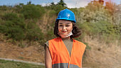 Portrait of a lovely cheerful young woman engineer or worker in a uniform and protective blue hardhat, smiling and looking at camera at construction site.