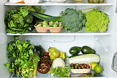Modern refrigerator with green vegetables. Healthy fresh nutrition. Healthy food and lifestyle