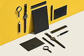 Black personal accessories, stationary flat lay on yellow and white background