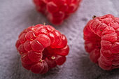 Fresh ripe raspberry fruit, summer vitamin red berry fruit on stone concrete background, angle view macro