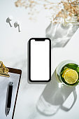 Smart phone mockup, template on table with cup of herbal tea