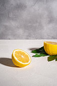 Two lemon slices, tropical citrus fruits with green leaves on white concrete background, angle view copy space