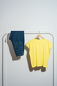 Yellow t-shirt and jeans displayed on clothes rack