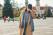 young pretty fashionable woman walking in brown coat by street