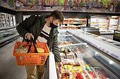 man choosing product in store fridge