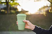 A woman holding a reusable coffee cup
