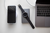 laptop with smart watch computer mouse and phone charging on wireless charger