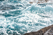 view of rocky seaside waves with white foam