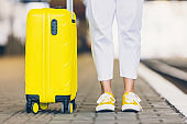 woman with yellow suitcase on wheels walking by railway station copy space