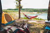 person view couple resting at camping woman laying in hammock with beautiful view of forest lake