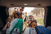 family with kid putting bag in car trunk