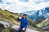 Young man using smart phone with view of Stelvio Pass in Italy