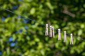 Outdoor clothesline with hanging clothespins. Sunny day with trees in background. Concept of housework, chores, laundry and energy cost savings