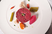 A chef prepares a gourmet dish of meat tartare and finishes the preparation with a touch of class.