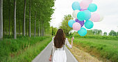 The young woman in a Victorian dress with colorful pastel balloons in a woods