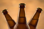 Brown full bottle of beer with water drops