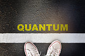 Quantum word written on asphalt road surface with white starting lines and sport shoe