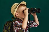 Little boy tourist with backpack looking through a binoculars.