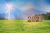 New year 2021 on grasses with wind turbines on mountain background