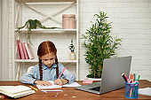 little child girl using laptop for studying online