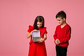 Happy little child boy gives smiling girl a gift box