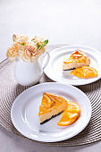 Slice of Orange Baked Cheese Cake on a gray background. Dessert Concept