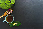 Tea time composition. Green iron teapot, cup of tea, wooden spoon with rose buds and green tea leaf
