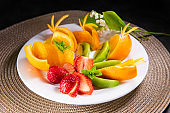 Delicious fruits in plate on black table