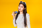 Tourist woman in summer casual clothes.Asian Smiling woman on yellow  colour background .She going to summer vacation surprise Sale.Travel trip funny Credit card on holiday.