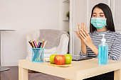 Asian people using alcohol antiseptic gel and wearing prevention mask .she working from home wearing protective mask.  Working from home with sanitizer gel.Against infection of Covid-19 outbreak,