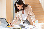 Architect or interior designer working with material sample board in showroom. Business of Real estate, home decoration .Creative people workplace.  young designer woman working with color palette at office desk.