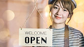 Business owner attractive young Asian woman in apron hanging we're open sign on front door smiling welcoming clients to new cafe. Beautiful Young Cafe Owner Turning Storefront Sign From Close to Open and Welcoming Her .