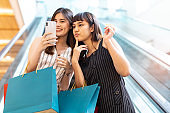 Asian woman wearing face mask. Happy woman with shopping bags enjoying in shopping.lifestyle concept.Smiling girl  holding colour paper bag.Friends walking in shopping mall.time shopping  coronavirus crisis or covid19 outbreak.