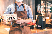 Business owner attractive young Asian man in apron hanging we're open sign on front door  welcoming clients to new cafe. Happy waiter with protective face mask holding open sign while standing at cafe .