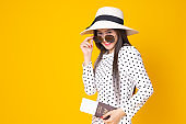 Tourist woman in summer casual clothes.Asian Smiling woman .Passenger traveling abroad to travel on yellow background.She going to summer vacation.Travel trip funny  on holiday.