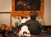 Bored child and dog staying at home during quarantine watching fire in fireplace