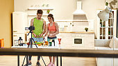 Best in Production. Young couple recording video blog or vlog about healthy nutrition on camera at home. Man and woman showing ingredients and explaining how to prepare, standing in the kitchen