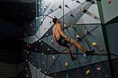 Man in safety equipment and harness having a break while training on the artificial climbing wall indoors