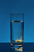 Close up of glass of water with effervescent aspirin tablet, pill in it isolated over blue background. Health concept