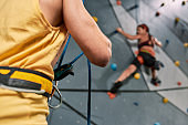 Cropped view of male instructor holding rope, while woman in safety equipment and harness training on the artificial climbing wall