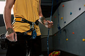 Chalked, locked and ready to rock. Cropped shot of sportive man holding rope, hands in white dust of magnesia, chalk, ready for climbing wall in bouldering center