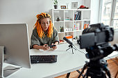Female technology blogger with dreadlocks using smartphone while recording video blog or vlog in the daytime