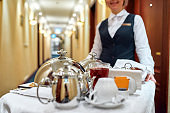 All that you need. Waitress in uniform delivering tray with food in a room of hotel. Room service. Focus on tableware