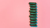 Creative concept with many green glitter pills lying in a row vertically isolated on pastel pink background. Minimal style, art concept