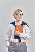 Portrait of elegant middle aged caucasian woman wearing business attire and glasses looking at camera, holding her notebook while standing isolated over grey background
