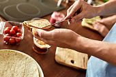 Close up of man spreading hummus onto toasted bread. Couple of vegetarians preparing healthy meal in the kitchen together. Vegetarianism, healthy food concept