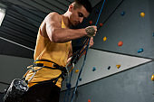 Young sportive man, rock climber holding rope, ready for training on the artificial climbing wall. Concept of sport life and climbing