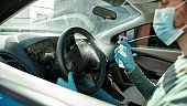 Cropped shot of man wearing medical mask and protective gloves spraying antibacterial disinfectant spray on steering wheel while cleansing car interior to prevent virus